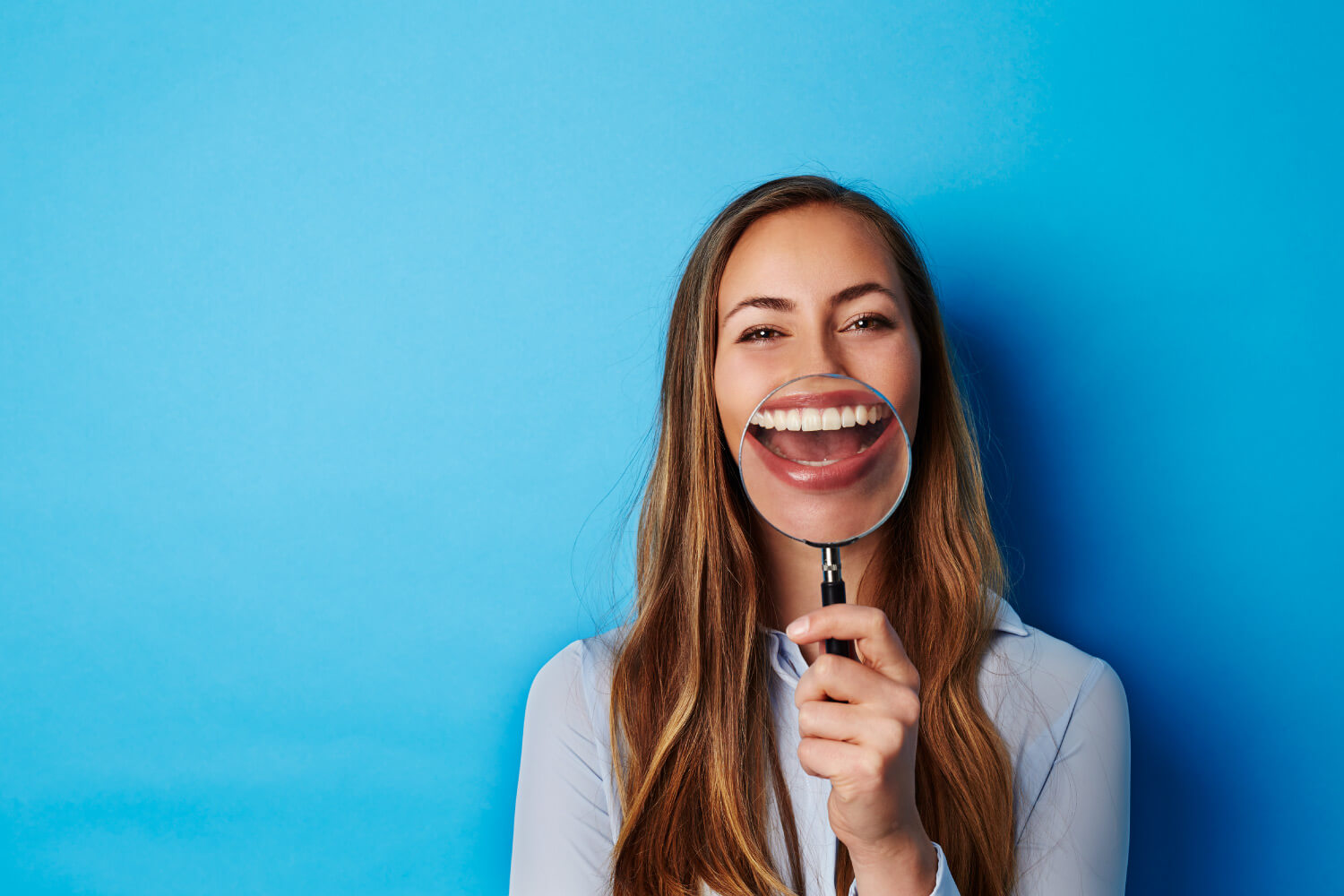 Brunette woman smiles and holds a magnifying glass to her teeth against a blue wall