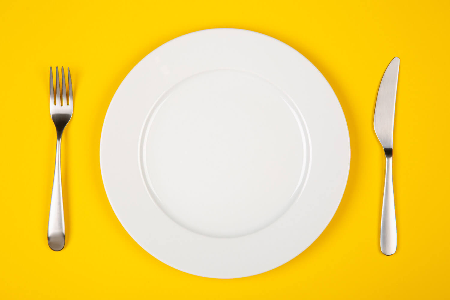 Aerial view of a white plate with silverware on a yellow table at a restaurant