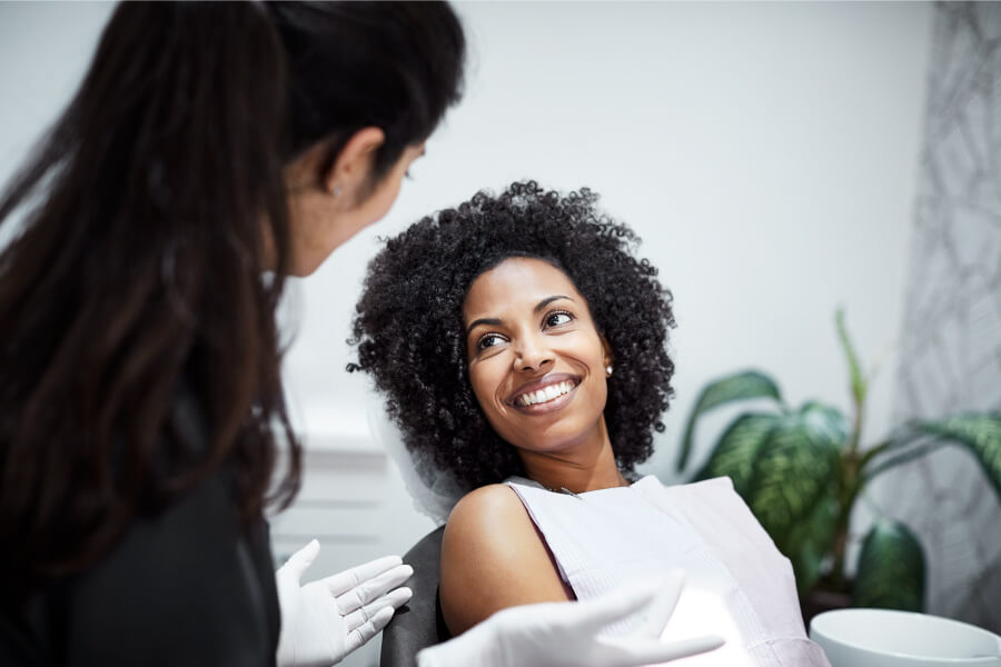 Brunette woman smiles after a successful smile restoration in Fayetteville, AR