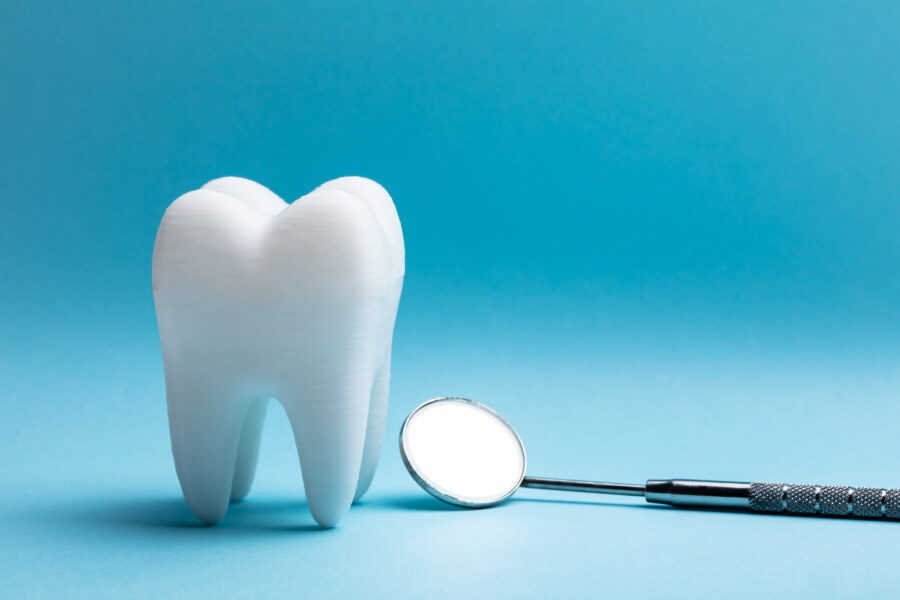 An extracted tooth next to a special dental mirror against a blue background